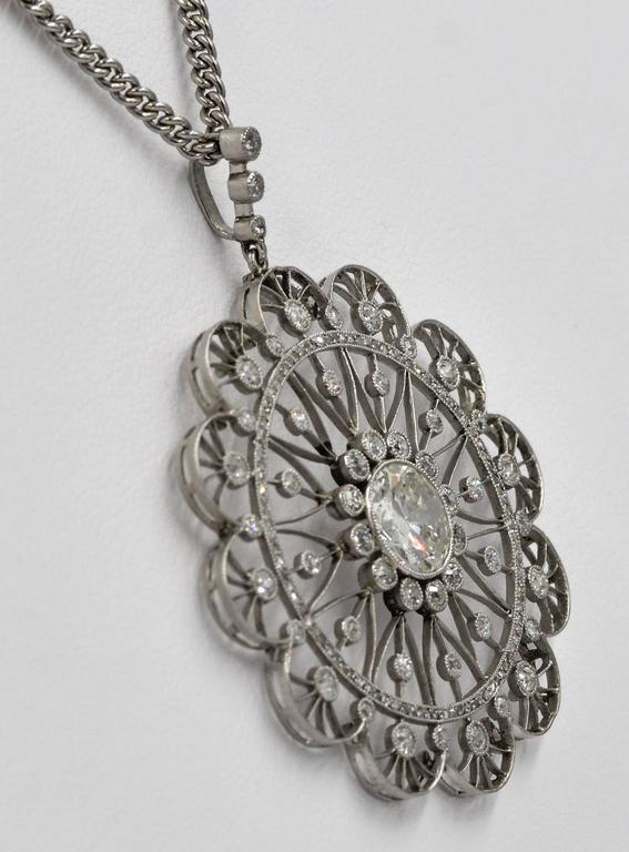 This platinum Edwardian pendant is a classic example of Edwardian design.  The pendant centers on a beautiful 1.75 carat round European cut diamond that is bezel set and surrounded by twelve Old Mine cut bezel set diamonds. Intricate lacy patterns