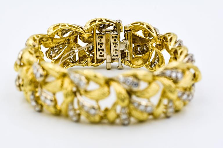 This stunning 18k yellow gold and diamond bracelet is executed with an attractive three dimensional textured paisley design.  The bracelet is set with 99 round brilliant cut diamonds with an approximate total weight of 1.25 carats G-H color and VS