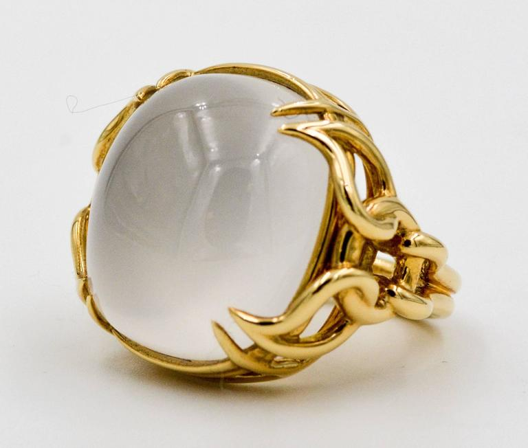 This is a prominent 26.00 carat white quartz cabochon ring crafted by Seaman Schepps in opulent 18kt yellow gold.  Seaman Schepps set the 26.00 carat white cushion cut cabochon quartz in an attractive interlocking weave pattering that begins in the
