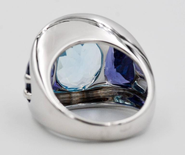 Seaman Schepps centered this amazing ring with an amazing oval faceted blue topaz that measures 15.22X12.00 mm.  Accenting and contrasting the rich blue of the oval topaz Seaman Schepps set two rich purple trapezoid cut iolite stones which measure