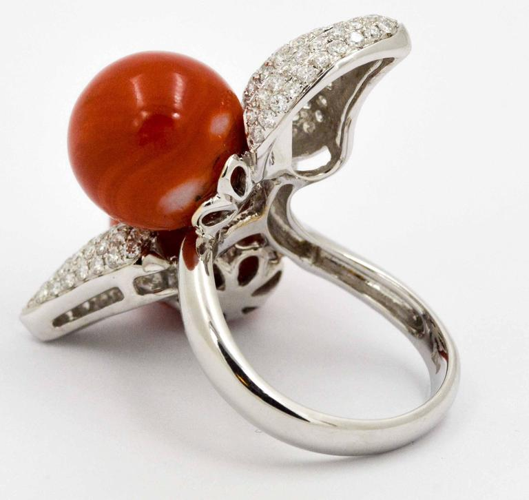 Be inspired by this beautiful Torro Del Coral Ring designed by DeSimone, featuring two charming round red coral beads that measure 12.35 mm each.  These pleasing red coral beads are artfully accented with three stunningly beautiful diamond pave
