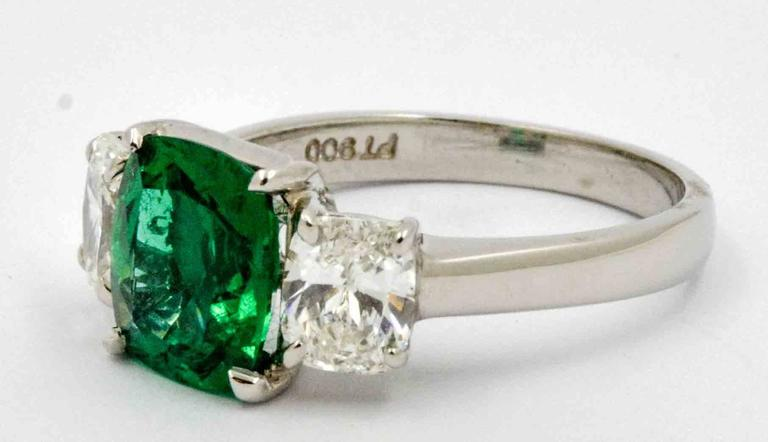 As green as the hills in Ireland, this rapturous platinum JB Star engagement ring is centered with a 1.80 carats vivid bright green cushion cut Emerald.  Accenting this amazingly bright green Emerald are two matching cushion cut diamonds that have a