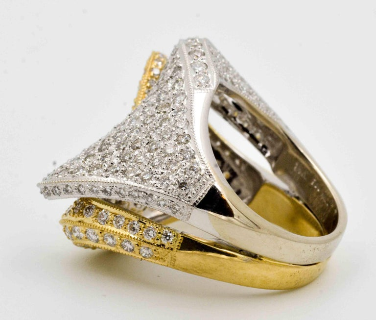 This incredibly amazing two color diamond fashion ring is crafted in an elegant paisley design which contrasts the rich 18 karat white gold against the 18 karat yellow gold.  Each half of the ring is pave' set with 134 round brilliant cut diamonds