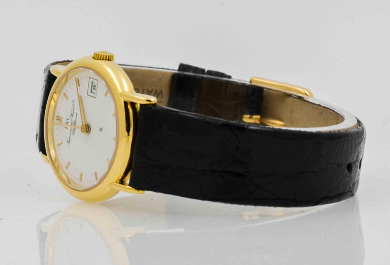 International Watch Company (IWC) 26 mm ladies watch in 18 Karat yellow gold with white index dial. Date, second hand, quartz movement. Black crocodile strap with Ardillion buckle. Certified pre-owned and recently serviced.