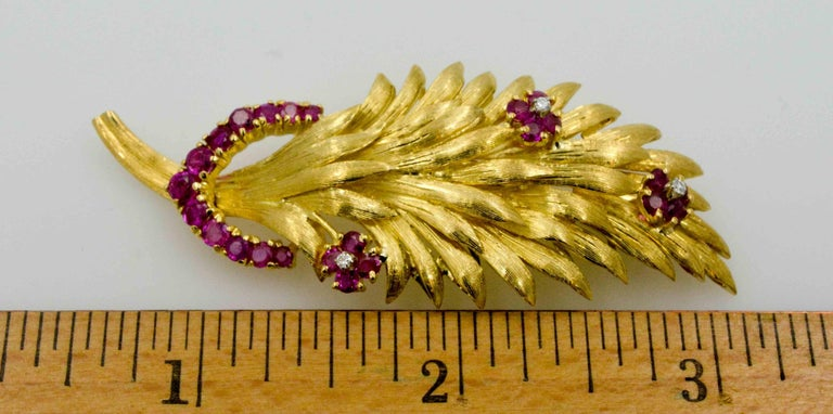 Bring back the retro look with this 1950's 18 karat yellow gold brooch sculpted as a wheat leaf with Ruby accent flowers and a diamond centered in each flower. This beautiful antique brooch has a trail of rubies (1.50 ctw) and single cut diamonds