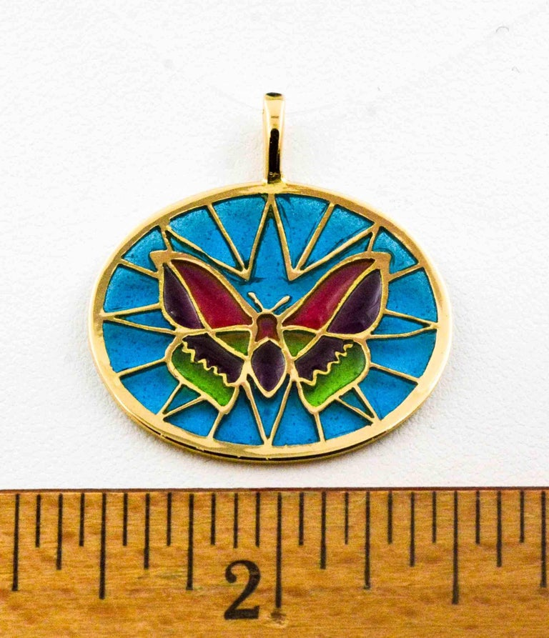 Bright red, green, and purple make up the body of this hand crafted Plique a Jour glass enameled butterfly. The beautiful background is a mesmerizing soft blue. The master craftsman created this  delicate little pendant in the art of Plique a Jour