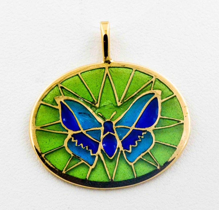 On a pale green background, a two color dark and light blue butterfly is crafted in the Plique A Jour glass enameling art. A master craftsman created this delicate little butterfly with hand enameling blues and greens with 18 karat yellow gold as