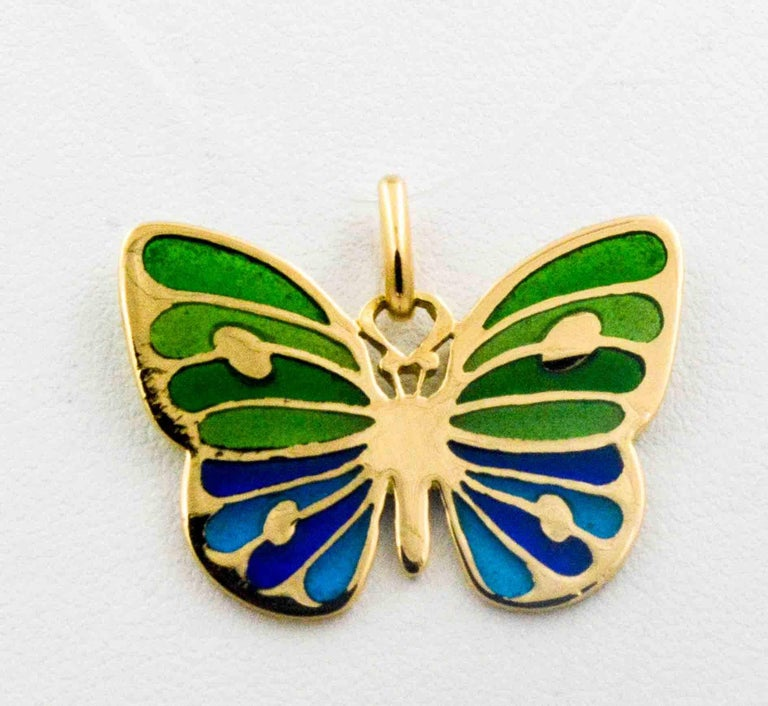 This charming little glass enameled butterfly, in hues of soft blues and greens, is hand crafted in the Plique a Jour art. 18 karat yellow gold accents the body and wings of this captivating delicate little butterfly.
