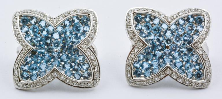 These eye catching designer Rodney Rayner clip-on earrings feature shimmering 18 karat white gold, sparkling blue topaz, and lovely accent diamonds. The blue topaz gems have a total weight of 5.52 carats, and the diamonds have a total weight of 0.89
