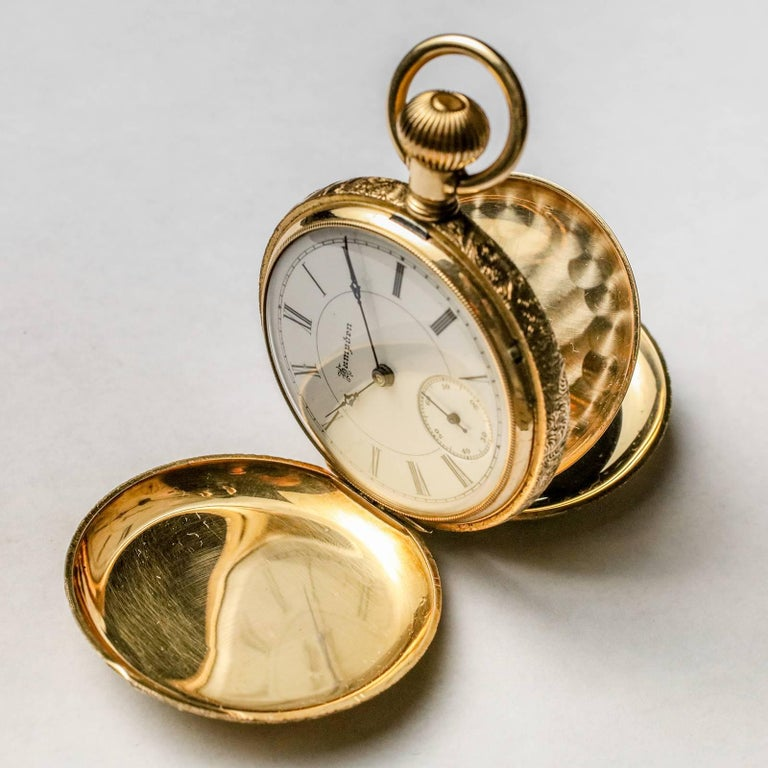 Large gold filled antique pocket watch by HAMPDEN Watch Co.  Case features multi-colored gold overlay with beautifully detailed flowers on both sides.  Large medallion on front can be engraved.  Unusual lever pulls out for setting time (vs. stem
