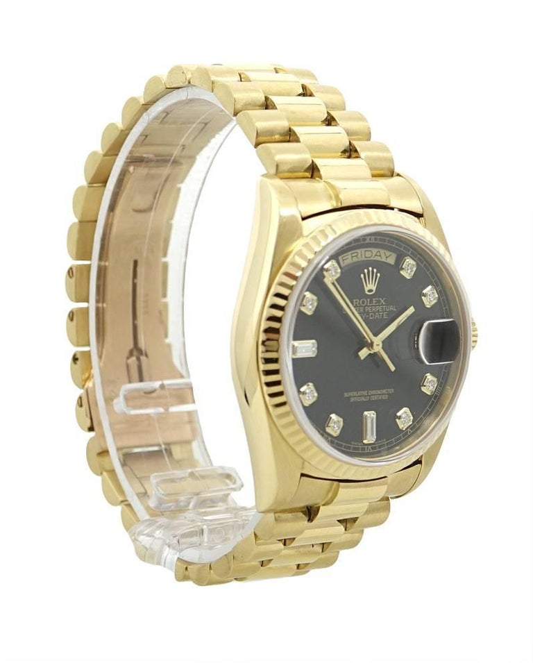 This Classic Rolex 18K Yellow Gold Day Date President Watch Has A Black Dial With Round and Baguette Shaped Dial Markers, And Gold Toned Hands. A Day and Date Indicator Can Also Be Found On This Dial. This Rolex Has A Fluted Bezel and A Concealed