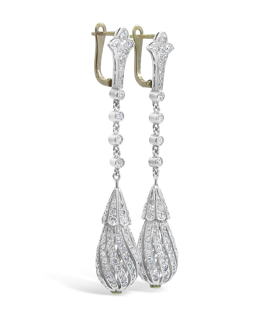 These beautiful vintage dangle earrings have approximately 2.50 carats total weight. There are 126 round old mine cut diamonds on each earring. The bottom teardrop spins on a ball to give them life. All diamonds are securely set in platinum and the