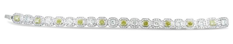 Beautiful bracelet is in 18k white gold with halo style alternating fancy yellow and white cushion cut diamonds with pave set round diamonds around each cushion cut diamond.