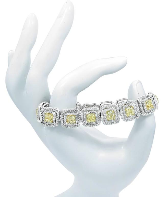 This 18k white gold tennis bracelet holds 14 cushion cut fancy yellow diamonds which equal 14.70cts with SI1-SI2 clarity. There are approximately 792 round brilliant cut colorless SI1 quality diamonds in the double halo surrounding each of the fancy