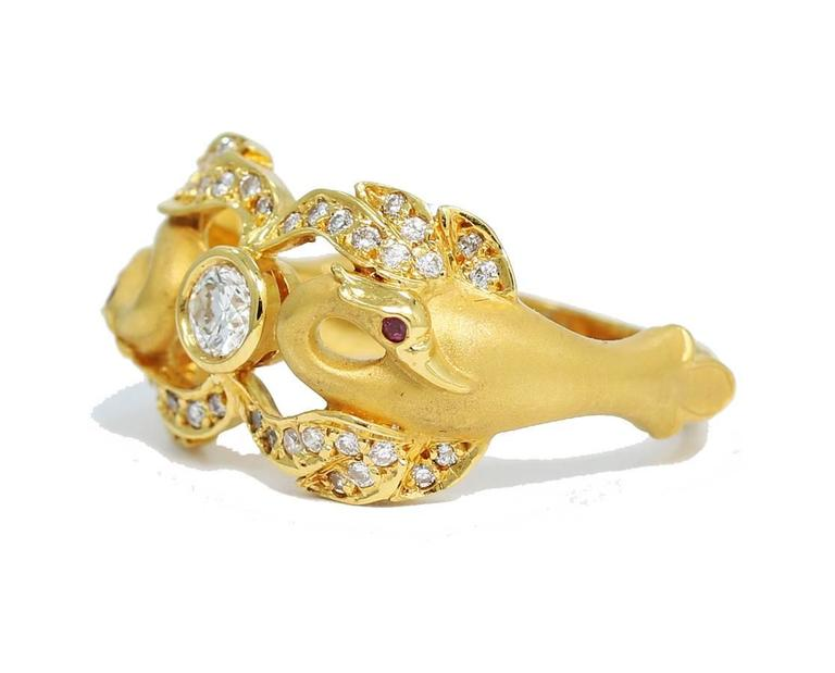 This Carrera Y Carrera double swan ring created in 18k yellow gold. Between the two swans holds a .21ct round brilliant cut diamond securely bezel set. Wings of the swans are composed of smaller round brillant cut diamonds and the eyes are of round