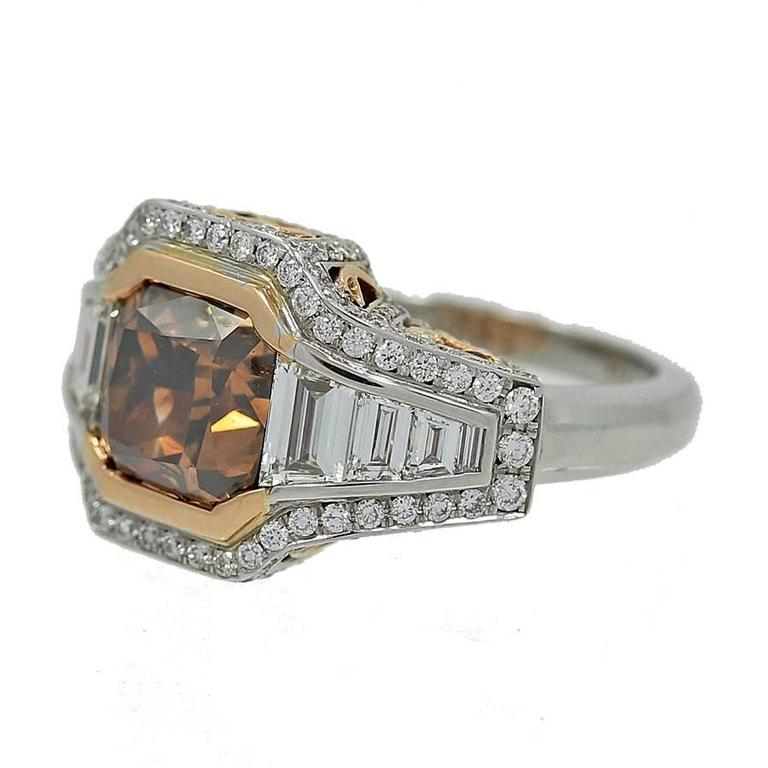 18K White Gold Ring with a Natural Fancy Dark Orangy Brown Cushion Cut Diamond weighing 4.01 carats and is SI2 in Clarity. the ring also features 1.19 carats in trapezoids, G Color VS Clarity and Round Brilliant Diamonds weighing 1.10 carats in