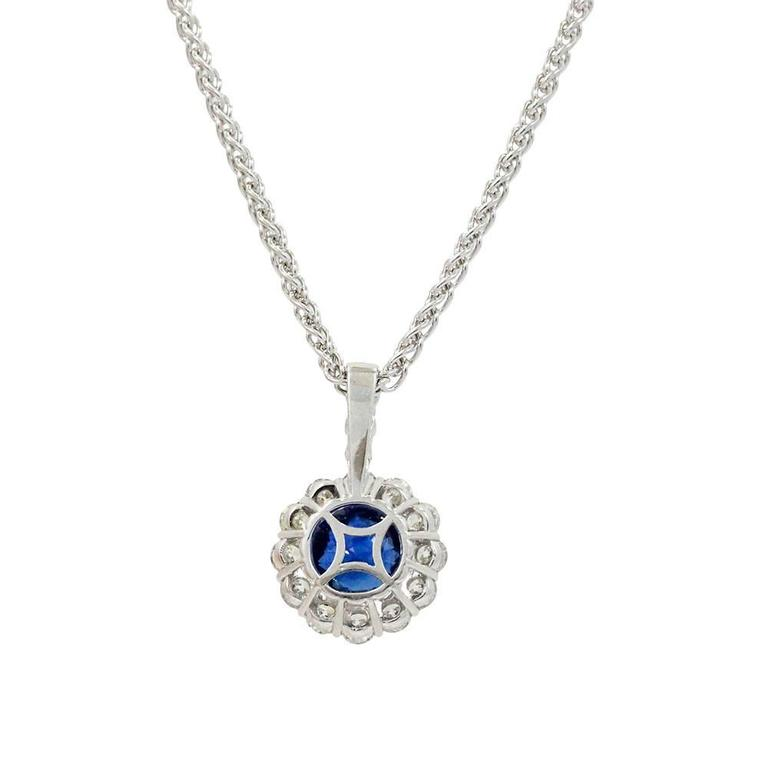18K White Gold Pendant With Center Sapphire Weighing A Total Carat Weight Of 4.35ct And Surrounding Diamonds Weighing A Total Carat Weight Of 2.19ct.