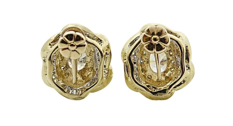 These 14K Yellow Gold Earrings are Shaped Like Flowers With Oval Cut Diamonds In The Center Of Each Earrings Weighing A Total Carat Weight Of 1.50 Carats, As Well As Baguette and Round Diamonds Weighing A Total Carat Weight Of .25 Carats. These