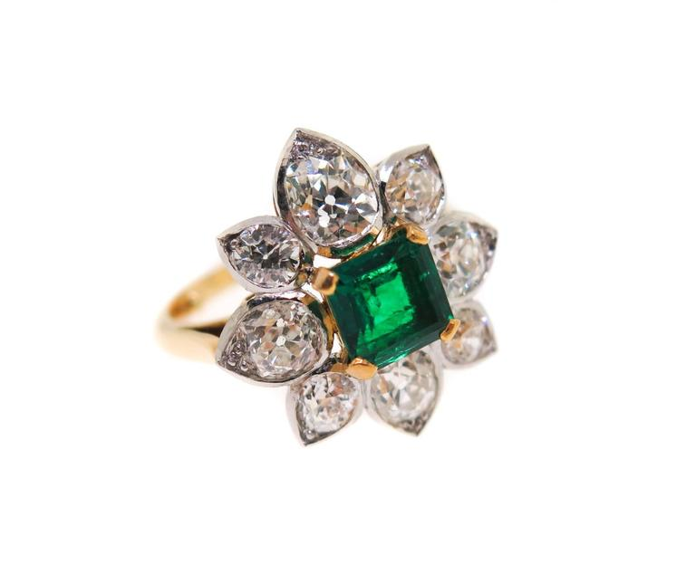A gorgeous ring, centered with a very fine princess-cut emerald (6.5 mm, approximately 1.50 carats) surrounded by a cluster of 8 old european cut diamonds. Estimated total diamond weight is approximately 2.50 carats. Crafted in 18K yellow gold and