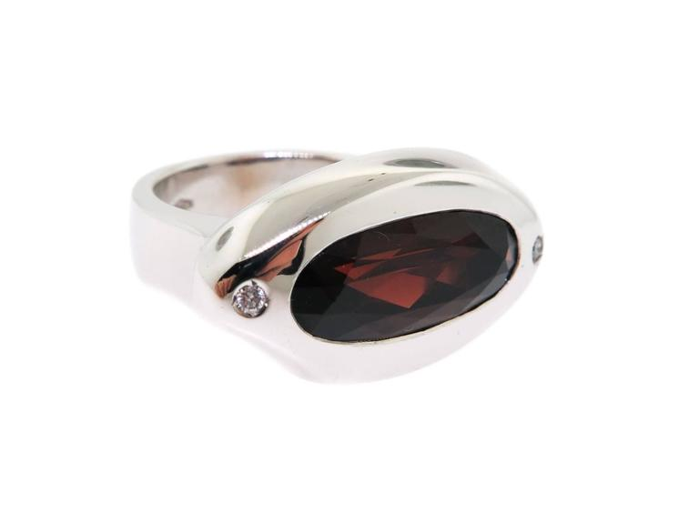 Eye-catching and compelling... wonderfully set garnet in a very attractive smooth 18 karat white gold bezel, exceptional design by Manfredi.