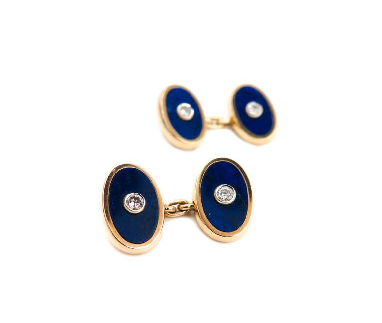 A pair of exquisite Cartier lapis lazuli and diamond cufflinks,  flat oval discs of lapis lazuli sprinkled with gold dust adorned with a bezel set round diamond center. Set within a bevelled mounting in 18K yellow gold, with chain fittings.  Signed