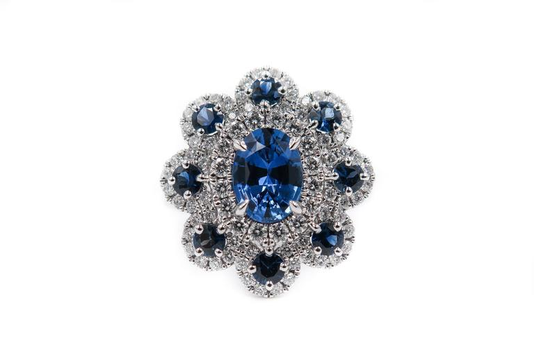 A gorgeous sapphire and diamond ring handcrafted in 18K white gold. The central oval shaped sapphire, weighing 1.40 carats, in a four claw setting, surrounded by round cut sapphires weighing 0.76 carats, each set in a halo of brilliant cut diamonds,