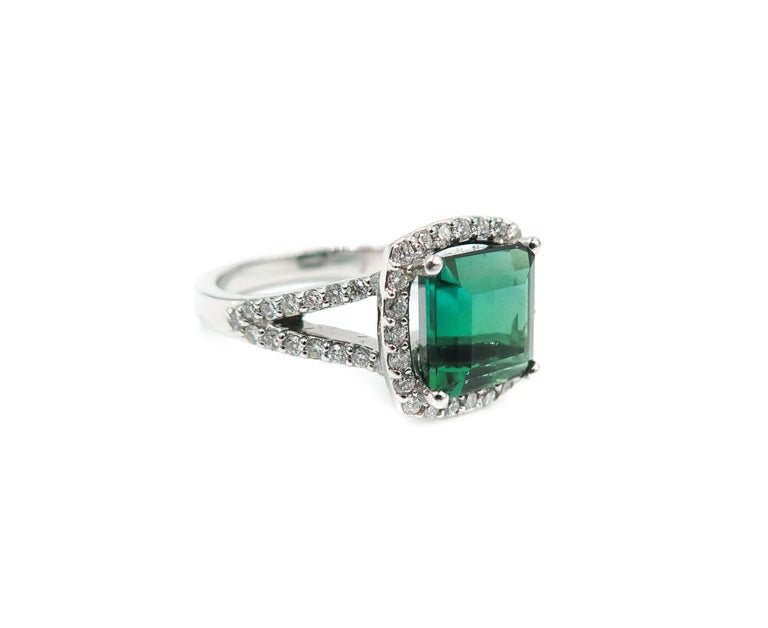 Intense and deep green colored tourmaline set in an exquisite ring.  Handcrafted in 18K white gold with a split shank diamond setting in size 7. The green tourmaline weighs 4.10 carats and 0.80 carats of diamonds. A classic ring that you'll enjoy