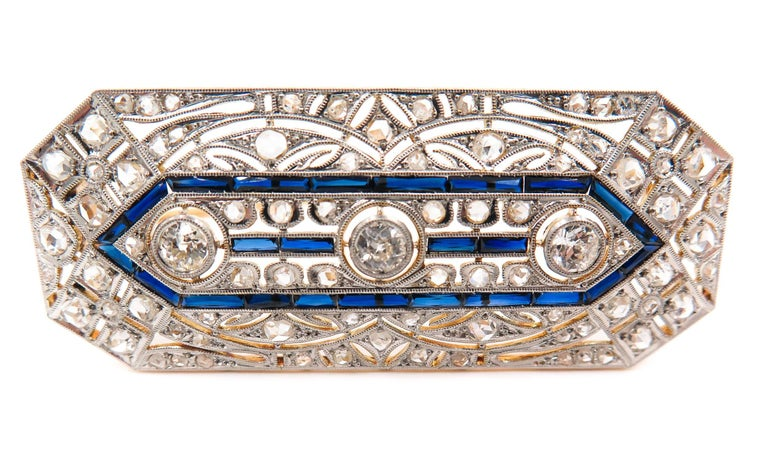Art Deco diamond and sapphire crafted in platinum and 18K yellow gold brooch.  Designed with 3 rose-cut diamonds framed by similarly cut diamonds and blue sapphire, an excellent quality jewel, high craftsmanship and outstanding beauty, characterized