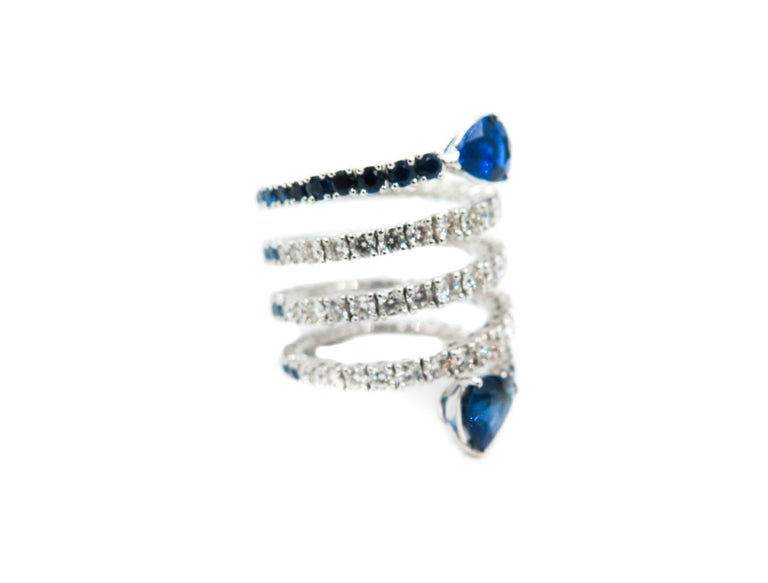 Each gemstone tells a different story and the combination develops into new tales .  This bi-color spiral ring is different from any other, it is created with the most beautiful color combination: sapphires and diamonds. Half of the spiral is a line
