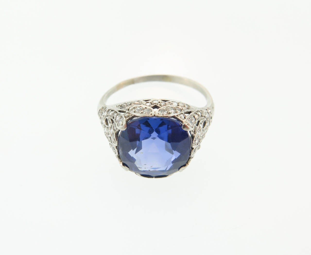 This stunning antique ring 1920's features an elegant filigree design hand-crafted in platinum and set with 69 old-mine diamonds. The center stone is a Natural Round Ceylon Sapphire (unheated) weighing 7.65 carats. The ring does not have any stamps,