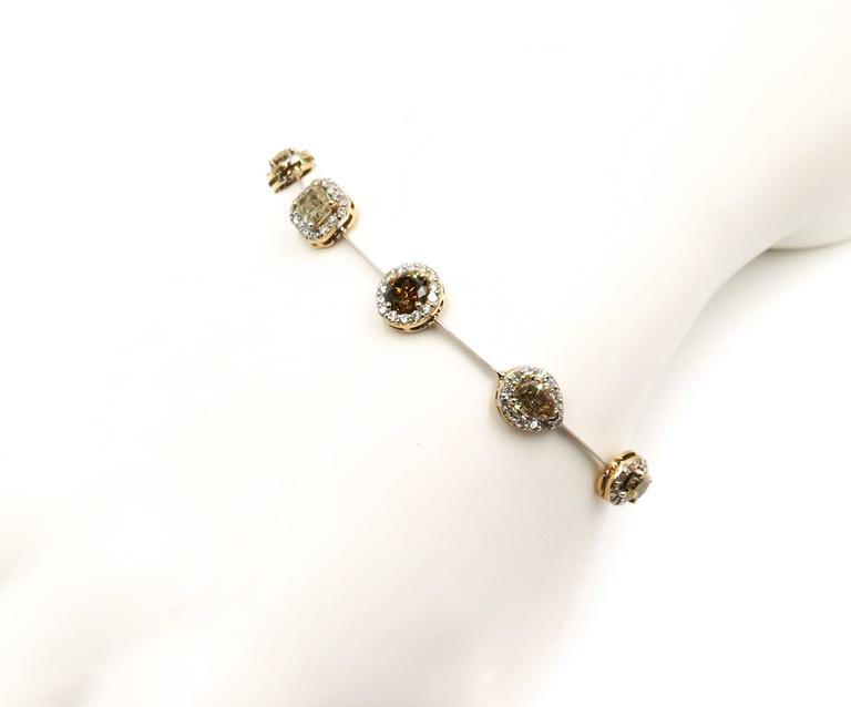 Stunning bracelet composed of 9 natural fancy colored diamonds in different shapes, weighing 6.99 carats surrounded by round brilliant cut diamond halo and handcrafted in 18 karat white and yellow gold.  Scientists believe these exquisite gems are