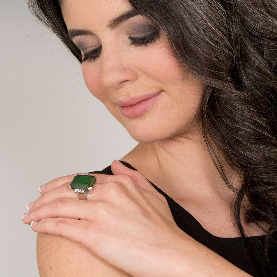 Circa 1960s, 18k, Swiss.  This sleek modernist ring is visually rife with notes of Industrial Design and Deco and ablaze with color. The look is glamorous with an emerald cut tourmaline of superb color and clarity at the center of the drama.