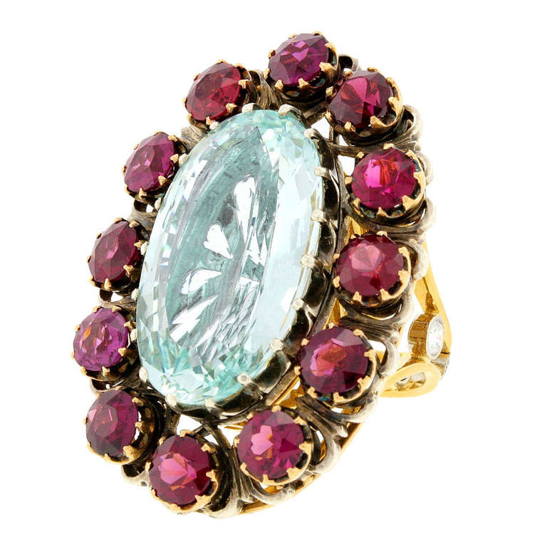 Circa 2012, Platinum and 18k, by Lawrence Jeffrey. This astonishing ring is set with a gorgeous 20-carat aquamarine surrounded by rare purple garnets. The under-gallery is completely handmade in eighteen-karat gold and platinum and specially