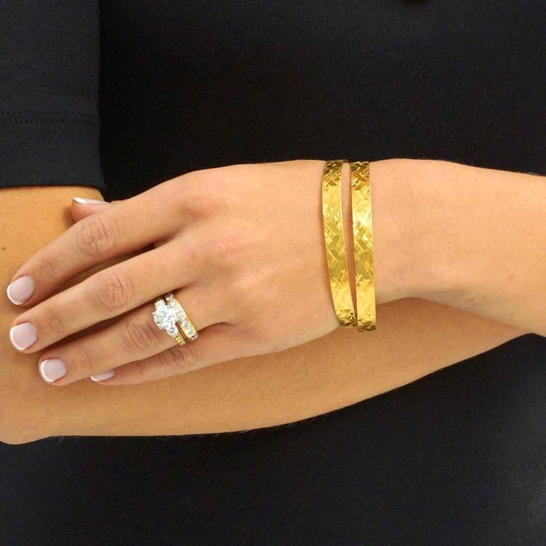 Circa 1960s, 18k. This fabulous pair of wide eighteen karat bangle bracelets are the epitome of casual, chic, Italian style. Timelessly sophisticated, the bright-cut stars interspersed with chevrons add visual interest and the meticulously engraved
