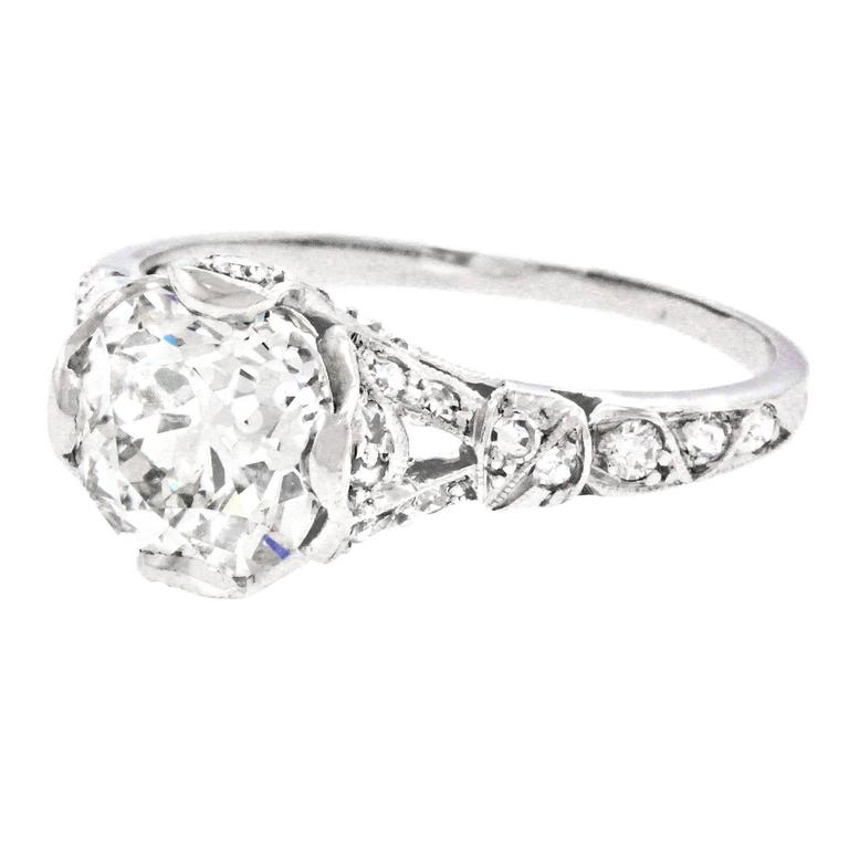 Circa 1920s, platinum, American.  This stunning Art Deco ring is set with a brilliant 2.03-carat old mine-cut center stone (J color and VS2 clarity) accented by an additional .40 carats of fine diamonds. A fluid geometry underscored by fine details
