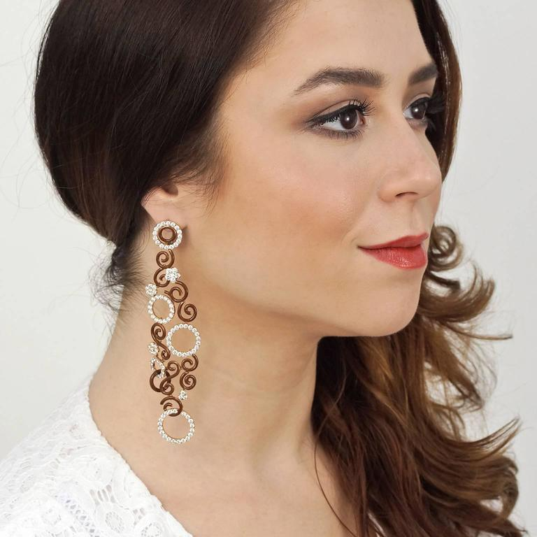 Circa 1970s, 18k, possibly Swiss.  These bold four-and-a-half-inch-long show-stopping earrings are nothing less than wearable works of art! Swirling plumes of luminous chocolate-hued enamel luxuriously entwine dazzling diamond-set circular and