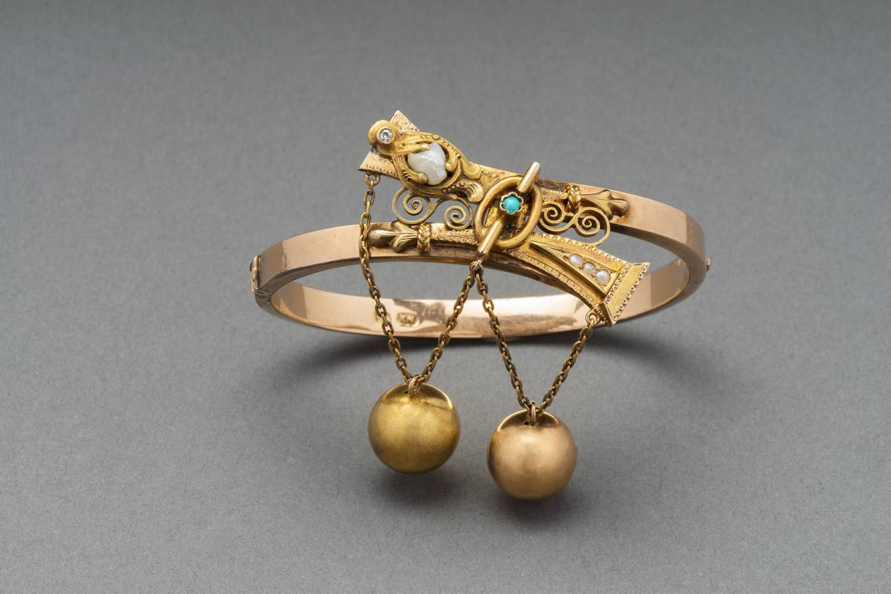 Of crossover design applied with Old Russian strapwork motifs and openwork scrolls, this two-color gold bangle from St. Petersburg is set with river pearls, a turquoise and a diamond and suspends two gold beads on small link chains. 