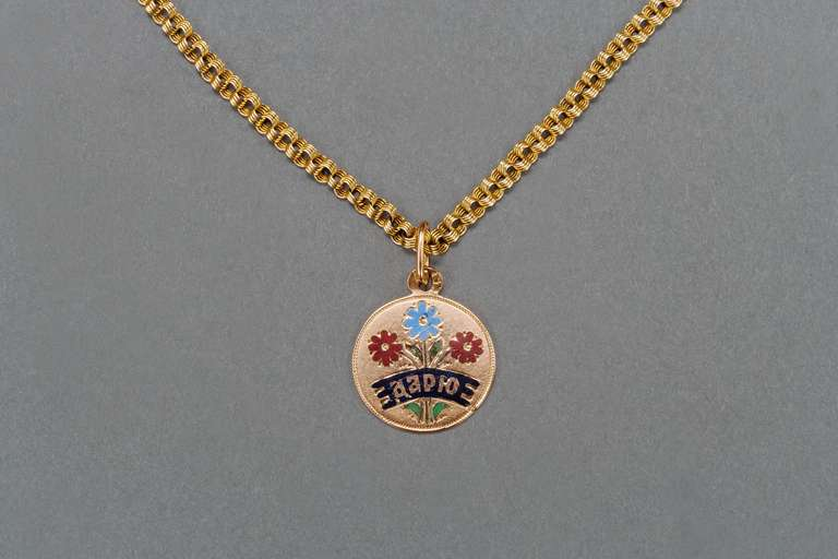The Romanov era gold pendant enamelled Daryou in Russian (tr: I give to you) above three enameled flowers on an original Russian gold chain with cylindrical clasp.  Russia, circa 1880, stamped 56 with maker's mark DA possibly for Dmitry Aksenov,
