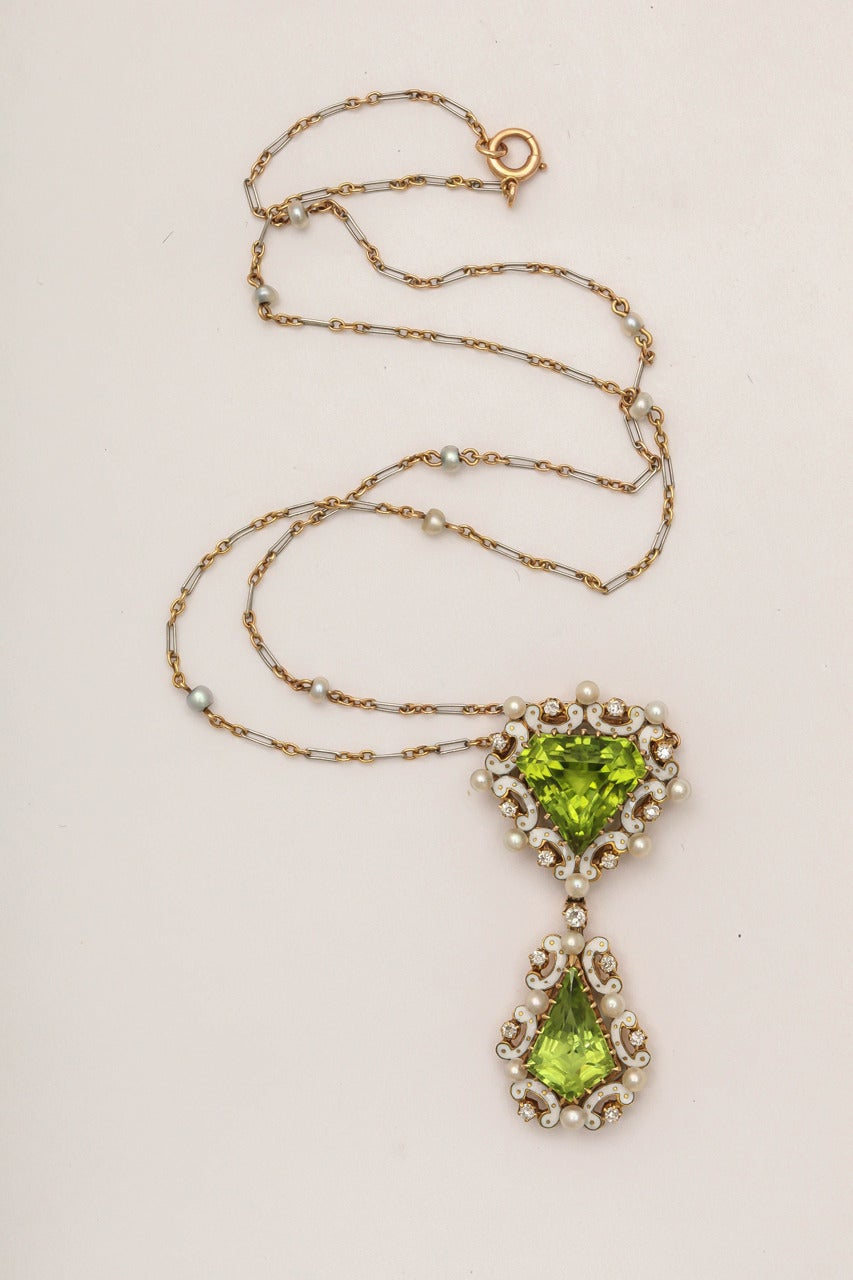 Set with two kite-shaped peridots of vibrant apple green color, each within white piqué enamel borders enhanced with natural seed pearls and diamond accents. Mounted in yellow gold, the central pendant is suspended from a pearl and two-color gold