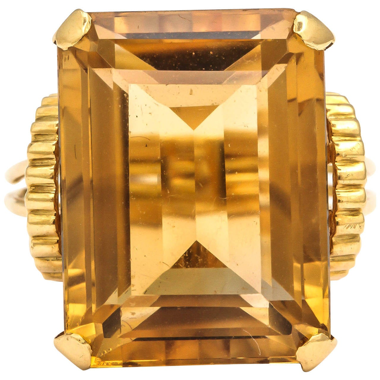 A 1950s English Retro Citrine gold statement ring, the 18k gold mount of openwork angular design, set with a rectangular-cut citrine weighing approx. 33 carats  Circa 1950.  Size  6 3/4