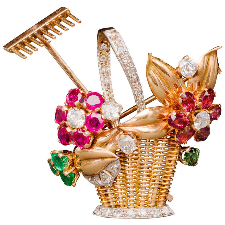 Of two color 18k gold, this delightful gardening pin from the 1940s is designed as a yellow gold hand-woven basket adorned with rubies, emeralds, pink and green tourmaline and diamond flowers, enhanced with polished rose gold leaves and a removable