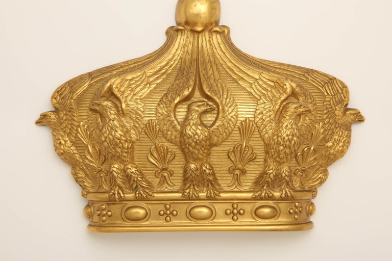 A wall mount of gilded bronze, after the Imperial Crown of Empress Eugenie (1826-1920), consort of Napoleon III. Featuring five perched eagles in high relief with upturned wings alternating with palmettes below a globe and cross.  7 1/4 x 6 1/4 x 1
