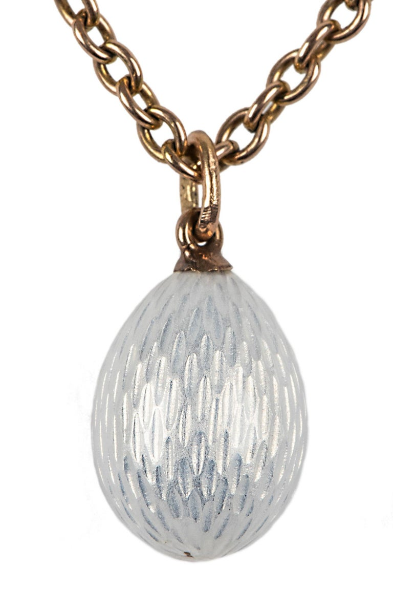 From the Romanov era, period of tsar Nicholas II, a rare Russian guilloché miniature egg pendant in translucent white enamel, enhanced with an oval cabochon sapphire bead set in a silver bezel, fitted with a gold suspension ring.   circa 1900,