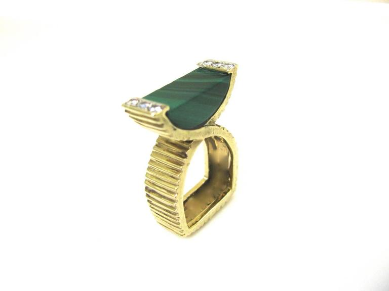 A modernist cocktail ring by La Triomphe. The 14k Yellow gold crossover ribbed shank with malachite flanked by .25cts of round white diamonds. Very pretty on . Elegant and Unusual.