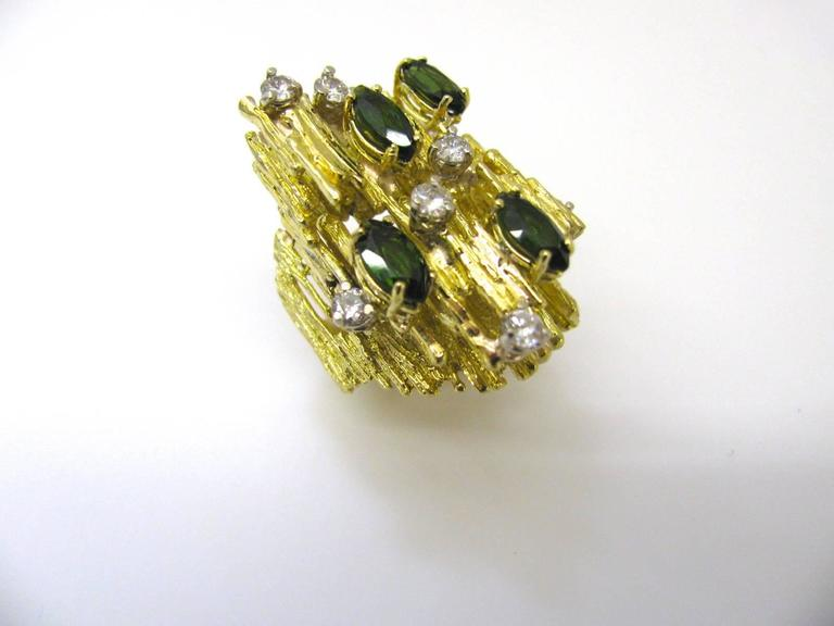 """An impressive green tourmaline and diamond 1970's fashion ring. The 1 1/4"""" x 5/8"""" 18k yellow gold freeform band ring with four navette shaped tourmaline and eight brilliant-cut round white diamonds weighing approximately .50cts total"""