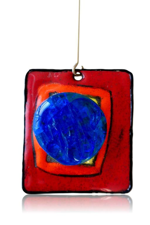 """Modernist Pierre Cardin Runway Jewelry. The choker necklace  with a 2 1/2"""" x 2 3/4"""" pendant made of geometric red, orange and yellow painted enamel featuring a brilliant blue glass boss, suspended from a 2 1/4"""" connector , on a large"""