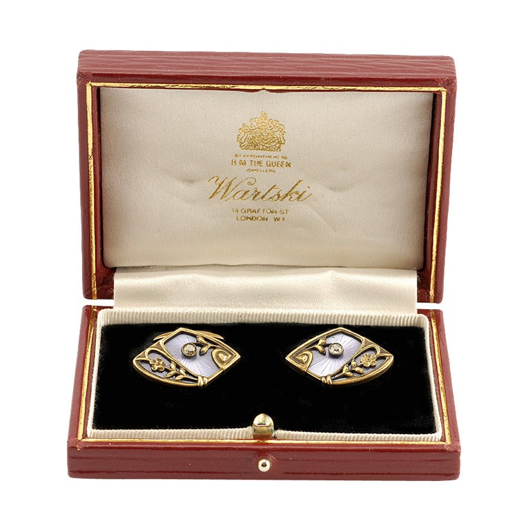 A pair of Russian antique 56 standard (14 KT) gold, guilloché enamel, and diamond cufflinks, 8th Artel, Moscow, 1908-1917. Of shaped navette form, the cufflinks with a green gold cagework with floral ornament, including a diamond-set blossom