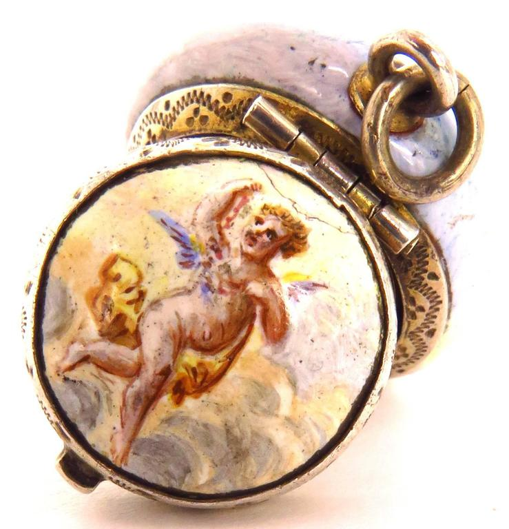 This wonderful porcelain vinaigrette has such a flow to it!. It's shaped like a miniature powder jar. The cover portrays a dog running with an angel. The bottom portrays 2 angels, one holding a lyre. When opened, the inside cover depicts a rose. The