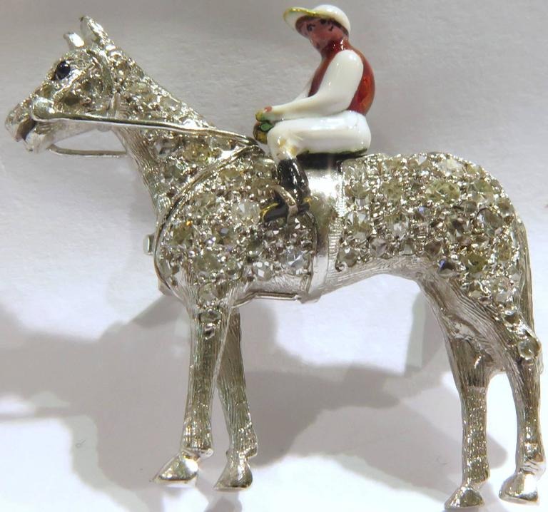 This awesome platinum equestrian pin features a diamond horse with an enamel rider holding the reins. The diamonds are a mixture of rosecuts & single cuts.  A must have for any horse enthusiast.  This pin measures 1 5/16 inch across by 1 5/16 inch