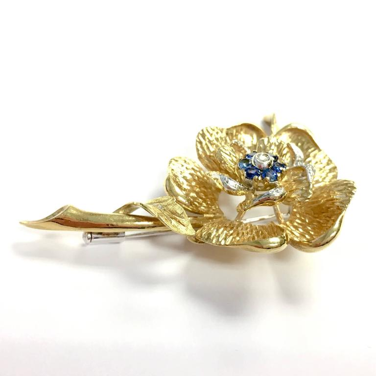 Crafted in 18K gold, the brooch features a sapphire and diamond floret in the center, surrounded by white and yellow gold diamond set petals. Bright polish and textured finish. Approximate total sapphire weight: 0.50ct. Approximate total diamond